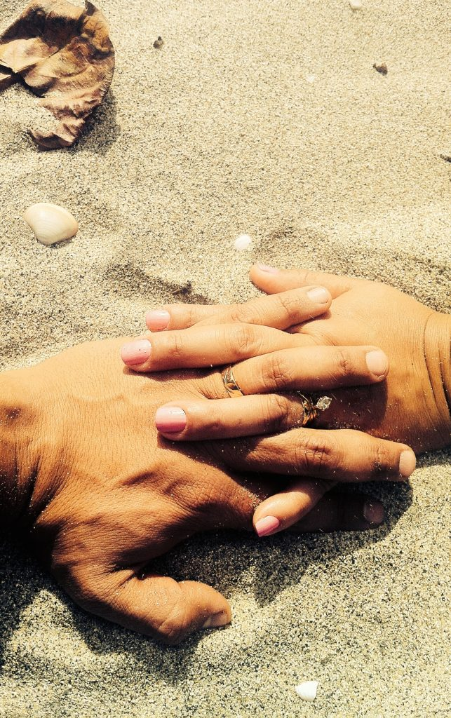 Male hand and female hands with fingers entwined.  Wedding rings sand.
